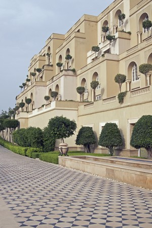 mughal: Luxury hotel built in the traditional Mughal style. Honey colored sandstone building with ornate tiled path. Agra, India