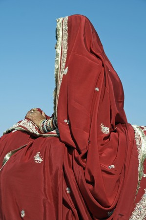 Indian lady in ornate red sari. Hands adorned with bangles and jewelery. Desert Festival Jaisalmer Rajasthan India.
