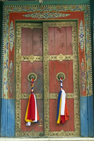 Old temple door decorated with tassels at Thikse Buddhist monastery. Ladakh, India