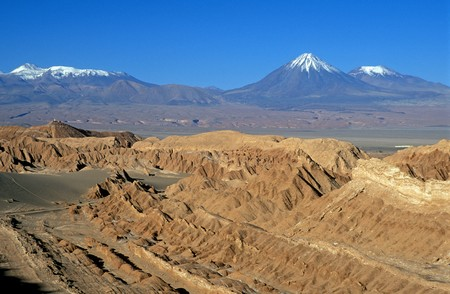erode: Natural rock formations of the Atacama Desert and beyond the snow capped peaks of the Western Cordilleras. Stock Photo