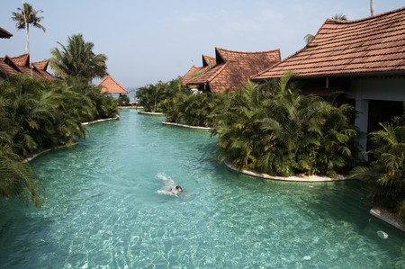 Lone swimmer in a large swimming pool between holiday chalets in the backwaters of Kerala India