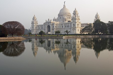 white marble: Victoria Memorial in Kolkata India. Ornate white marble building reflected in an ornamental lake at dusk. Stock Photo