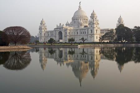 Victoria Memorial in Kolkata India. Ornate white marble building reflected in an ornamental lake at dusk. Standard-Bild