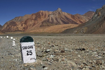 Road sign (25km to Sarchu) on the road between Manali and Leh high in the mountains of Ladakh, India photo
