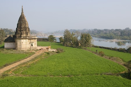 madhya: Old Hindu temple surrounded by lush green fields in Orchha Madhya Pradesh India Stock Photo