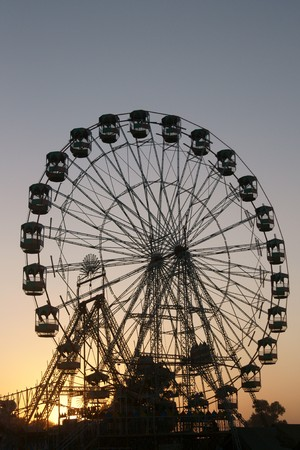 silhouetted: Ferris wheel silhouetted against the darkening sky as the sun sets over the Pushkar fair in Rajasthan India Stock Photo