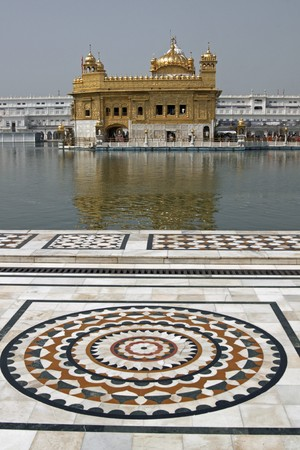 holiest: Golden Temple. Holiest shrine of the Sikh religion. Ornate marble around the pool of water containing an ornate building covered in gold. Amritsar, Punjab, India.