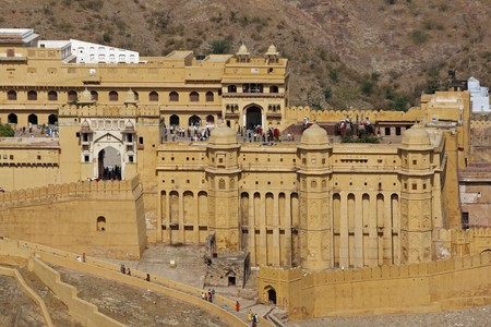 amber coloured: Amber Fort near Jaipur, Rajasthan, India. Large historic building covered in amber coloured plaster. Former home to the Maharajah of Jaipur. Elephants unloading tourists visible inside the courtyard.
