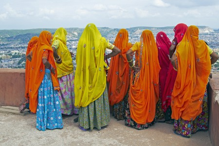 rajasthan: Indian women in brightly colored saris on the roof of a Rajput palace. Tiger Fort Jaipur Rajasthan India