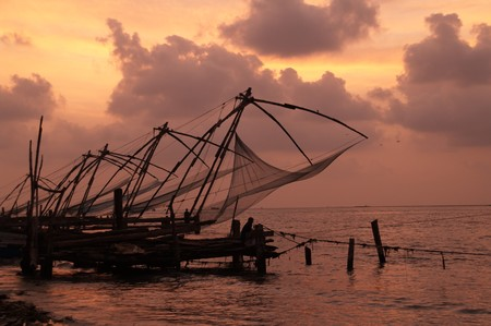 chinese fishing nets: Chinese fishing nets against sunset sky. Large wooden poles supporting fishing nets. Fort Kochi Kerala India