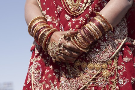 jewel hands: Hands of an Indian bride adorned with jewelery bangles and painted with henna.