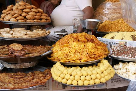 proprietor: Piles of Indian sweets on display at a shop in Pushkar, Rajasthan. Rotund body of proprietor visible.