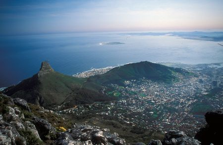 View of Cape Town from Table Mountain. The rugged peak of Lion Head and Signal Point surrounded by the city. Ocean beyond.
