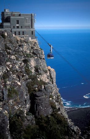 Cable car approaching the station on top of table Mountain, Cape Town, South Africa. Blue expanse of the sea beyond.