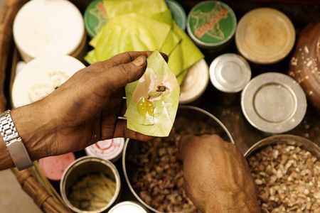 spat: Man making Paan on a street in Old Delhi India. A traditional mix of areca nut and spices wrapped in a betel leave which is chewed and then spat out.