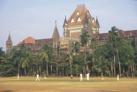 played: Large victorian gothic style building in the centre of Mumbai. Cricket match being played in the park in front. Stock Photo