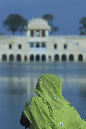 sagar: Indian lady in colorful sari looking out over the Water Palace (Jal Mahal) in the middle of Man Sagar lake. Jaipur, Rajasthan, India. 18th Century Stock Photo