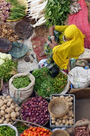 fruit and veg: Indian lady in yellow sari selling fruit and veg at a street market in Pushkar, Rajasthan, India Stock Photo