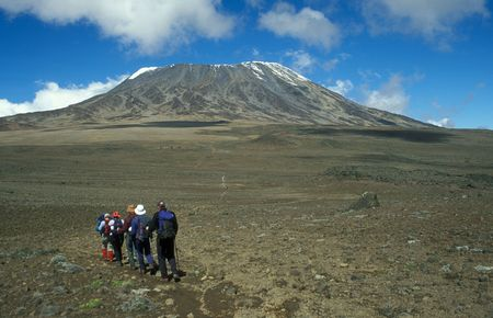 Group of walkers heading for the snow capped Mount Kilimanjaro, Tanzania, Africa