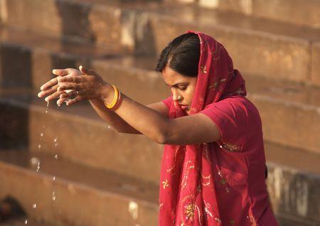 rituales: Benar�s, India - 12 de octubre de 2007: Dama hind� haciendo una ofrenda a los dioses en el r�o Ganges en Varanasi, India
