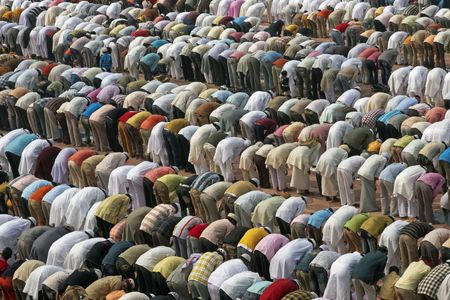 Agra, India - October 2, 2008: Thousands of people bending in prayer in front of the mosque at the Taj Mahal to celebrate the Muslim festival of Eid ul-Fitr in Agra, Uttar Pradesh, India