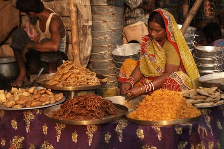 Sonepur, Bihar, India - November 28, 2007: Woman in brightly colored sari selling indian sweets from a market stall at the Sonepur Mela in Bihar, India.