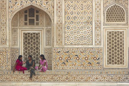 Agra, Uttar Pradesh, India - July 26, 2008: Group of Indian teens in colorful sari's sitting in the alcove of a beautiful Mughal Tomb, I'timad-ud-Daulah in Agra, Uttar Pradesh, India  Publikacyjne