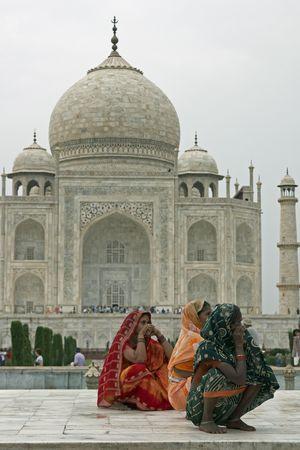 mughal architecture: Agra, Uttar Pradesh, India - July 26, 2008: Indian ladies in colorful saris squatting on a white marble plinth at the Taj Mahal in Agra, Uttar Pradesh, India