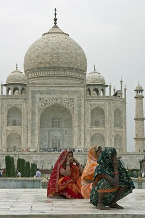 Agra, Uttar Pradesh, India - July 26, 2008: Indian ladies in colorful sari's squatting on a white marble plinth at the Taj Mahal in Agra, Uttar Pradesh, India Publikacyjne