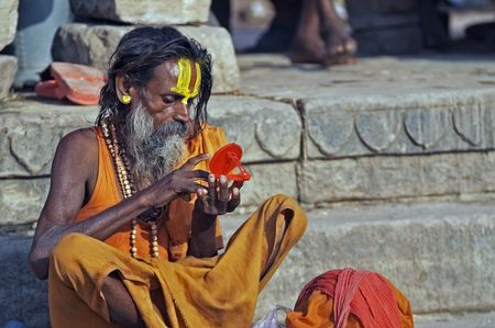 Varanasi, Uttar Pradesh, India - October 12, 2007: Religious man in saffron colored robes decorating his forehead with paint, Varanasi, India