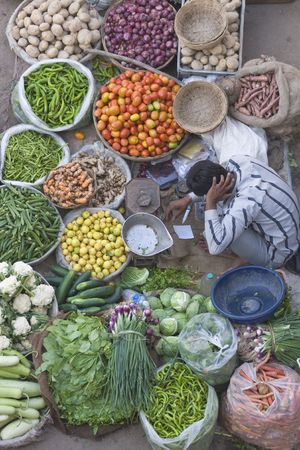 Pushkar, India - November 8, 2008: Man selling fruit and veg at a street market in Pushkar, Rajasthan, India