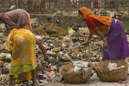 Calcutta, India - December 20, 2008: Indian women in brightly colored clothing sort through piles of rubbish in Calcutta West Bengal India. Stock Photo - 7115251