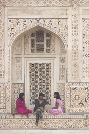 uttar: Agra, India - July 28, 2008: Indian teens in colorful saris sitting in the alcove of a beautiful Mughal Tomb, Itimad-ud-Daulah in Agra, Uttar Pradesh, India