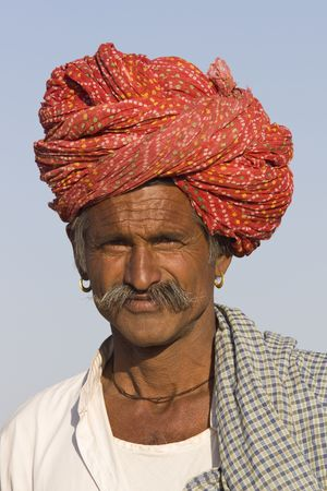 rajasthan: Nagaur, India - February 16, 2008: Rajasthani man with bright red turban and bushy mustache at the Nagaur Cattle Fair in Rajasthan, India