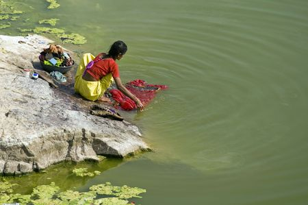 Chittaugarh, India - November 14, 2007: Indian lady washing clothes in a lake