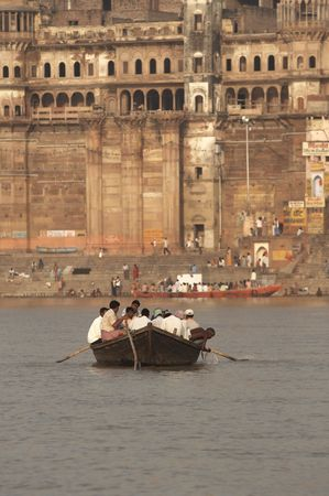 ganges: Varanasi, India - October 11, 2007: Boat full of people being rowed across the Ganges River at Varanasi, India