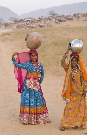 Pushkar, India - November 19, 2007: Colorfully dressed Rajasthani women collecting water using pots balanced on their heads. Rajasthan, India