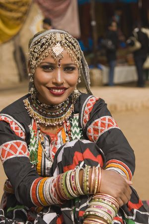 haryana: Beautiful Kalbelia dancer in ornate black costume trimmed with beads and sequins at the Sarujkund Fair near Delhi in India.
