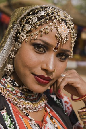 sarujkund: Beautiful Kalbelia dancer in ornate black costume trimmed with beads and sequins at the Sarujkund Fair near Delhi in India.