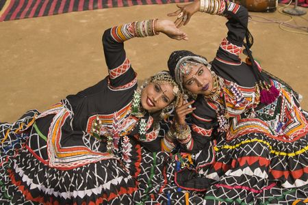 Beautiful Kalbelia dancers in ornate black costumes trimmed with beads and sequins at the annual Sarujkund Fair near Delhi, India. Stock Photo - 7713368