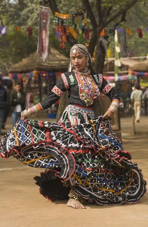 sarujkund: Beautiful Kalbelia dancer in ornate black costumes trimmed with beads and sequins at the annual Sarujkund Fair near Delhi, India.