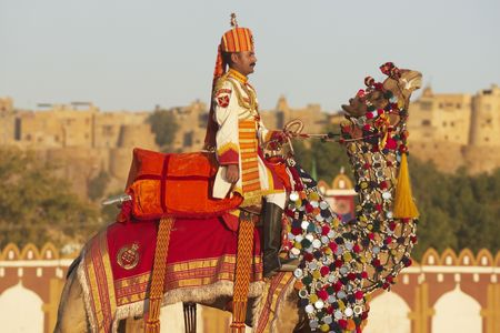 Jaisalmer, Rajasthan, India - February 20, 2008: Uniformed officer in brightly coloured uniform riding a camel in front of Jaisalmer Fort. Desert Festival, Jaisalmer, Rajasthan, India