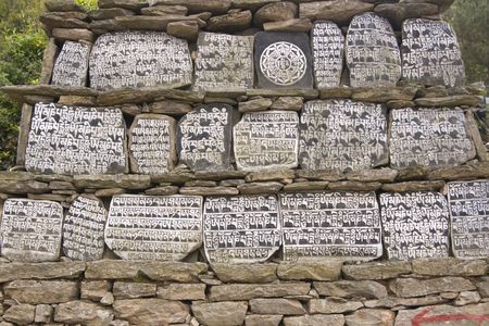 mani: Buddhist Mani stones inscribed with religious text on a wall in Nepalese Himalaya. Nepal Stock Photo