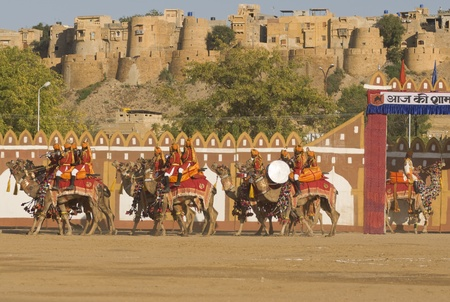 Jaisalmer, Rajasthan, India - February 20, 2008: Camels and riders of the Indian Border Security Force perform a riding exhibition in front of Jaisalmer Fort. Desert Festival, Jaisalmer, Rajasthan, India