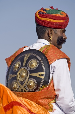 Jaisalmer, Rajasthan, India - February 1, 2007: Indian man in turban and with shield over his back at the desert festival in Jaisalmer, India Stock Photo - 8465060