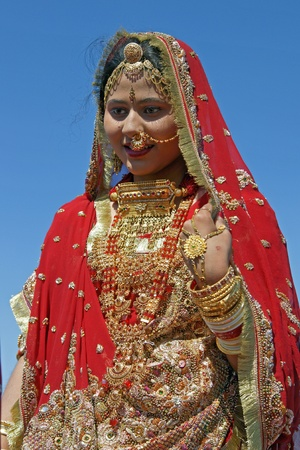 indian fabric: Jaisalmer, Rajasthan, India - February 19, 2008:  Indian lady dressed in ornate red sari and adorned with traditional Indian jewelery in Jaisalmer, Rajasthan, India.