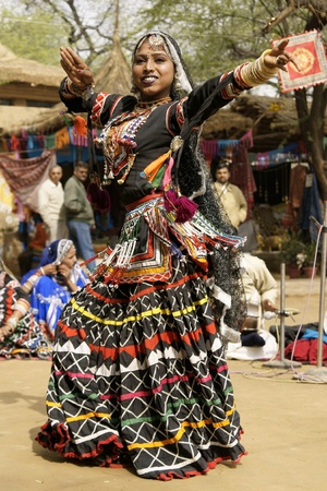 kalbelia: Delhi, India - February 12, 2009: Rajasthani dancer in ornate black costume trimmed with beads and sequins performing at the Sarujkund Fair near Delhi in India.
