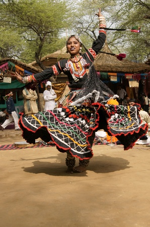 delhi: Delhi, India - February 12, 2009: Rajasthani dancer in ornate black costume trimmed with beads and sequins performing at the Sarujkund Fair near Delhi in India.