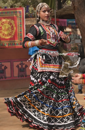 Female kalbelia dancer in traditional tribal dress performing at the annual Sarujkund Fair near Delhi, India photo