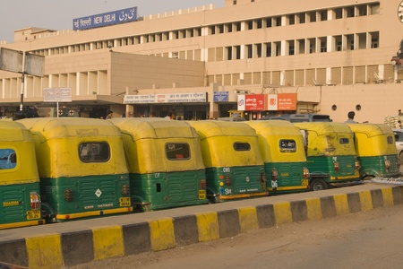 ew Delhi, India - February 5, 2009: Row of yellow auto rickshaws outside New Delhi railway station in Delhi, India